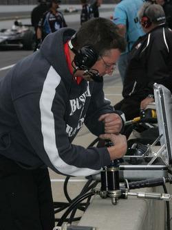 A crew member for A.J. Foyt Enterprises works on shocks