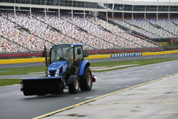 A Charlotte Motor Speedway track worker works on drying the track